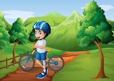 Ein Junge, der mitten in der Bahn mit seinem Fahrrad steht stock abbildung