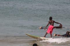 Ein Junge in der roten Hosenfahrt auf den Kamm von Wellen in Lagos-Strand, Bewunderer schauen an stockfoto