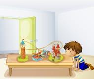 Ein Junge, der seine Spielwaren betrachtet Stockbild
