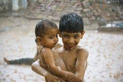 Ein Junge, der seinen kleinen Bruder vor starkem Regen schützt Lizenzfreie Stockfotos