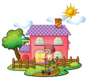 Ein Junge, der vor dem großen rosa Haus spielt Stockfotografie
