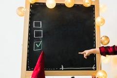 Ein Junge, der Wahlen auf einer Tafel mit copyspace überprüft stockfotografie