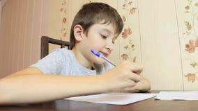 Ein Junge, der zu Hause durch die Tabelle sitzt und mit einem Stift auf Papier schreibt stock video footage