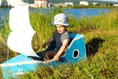 Ein Junge in einem behelfsmäßigen Schiff auf dem Seeufer Lizenzfreie Stockfotografie