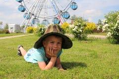 Ein Junge in einem Hut, der auf dem Gras im Park liegt lizenzfreie stockfotos
