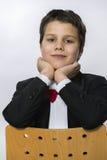 Ein Junge in einem Kittelmantel auf dem Stuhl mit seinem Kopf in seinen Händen Stockfotos