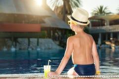 Ein Junge in einem Strohhut mit einem Cocktail in der Hand, das auf dem Pool sitzt stockfotografie