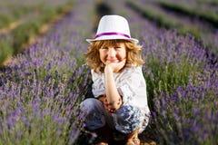 Ein Junge in einem weißen Hut, der Spaß auf dem Lavendelgebiet hat lizenzfreie stockbilder