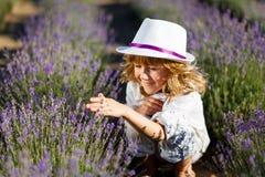 Ein Junge in einem weißen Hut, der Spaß auf dem Lavendelgebiet hat stockfoto