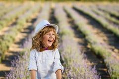 Ein Junge in einem weißen Hut, der Spaß auf dem Lavendelgebiet hat stockbild