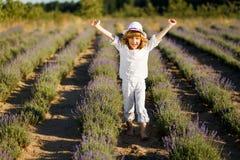 Ein Junge in einem weißen Hut, der Spaß auf dem Lavendelgebiet hat stockfotos