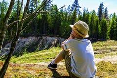 Ein Junge in einem weißen T-Shirt und in einem Hut sitzt am Rand einer Klippe im Wald und untersucht durchdacht den Abstand Stockfoto