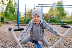 Ein Junge in einer grauen Klage nimmt an des im Freien Simulatoren Sports auf dem Spielplatz im Freien im Sommer teil Lizenzfreie Stockfotos