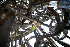 Ein Junge in einer merkw?rdigen Architekturstruktur Kunstbau machte vom Holz und vom Metall Gegenstand im Kunstpark von Nikola Le lizenzfreie stockfotos