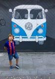 Ein Junge in Form eines Barcelonas FC nahe einer Graffitimalerei eines Volkswagen-Busses malte auf einer Wand stockbild
