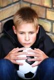 Ein Junge gegen eine Wand mit einer Kugel Lizenzfreies Stockbild