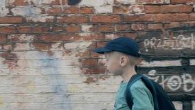 Ein Junge geht entlang weiße Backsteinmauer stock video footage