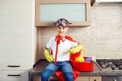 Ein Junge gekleidet als Superheld in der Küche lizenzfreies stockfoto