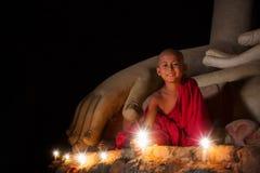 Ein Junge in gesetztem Feuer des Buddhismus mit Kerze in bagan lizenzfreie stockfotos