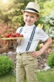 Ein Junge hält eine Platte der reifen aromatischen Erdbeere lizenzfreie stockfotos