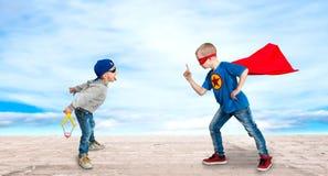 Ein Junge im Kostüm eines Superhelden, unterrichtet einen kleinen Tyrann zu den Regeln des guten behavio stockbilder