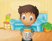 Ein Junge innerhalb des Hauses mit einem Glas Süßigkeiten Stockbild