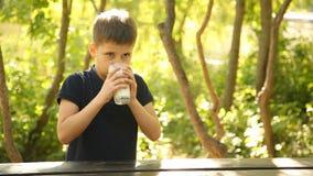 Ein Junge ist Trinkmilch an einem Tisch in der Natur stock video