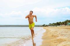 Ein Junge läuft aktiv auf dem Wasser nahe dem Wasser Stockfotos