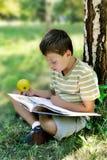 Ein Junge mit Apfel liest Buch am Baum Lizenzfreies Stockbild