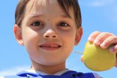 Ein Junge mit einem Apfel Lizenzfreies Stockbild