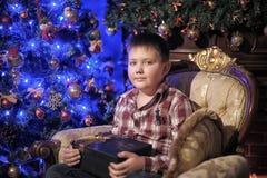 Ein Junge mit einem Geschenk, das auf einem Stuhl sitzt Stockfotos