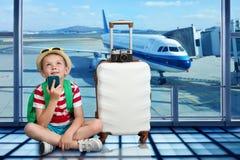 Ein Junge mit einem Koffer sitzt am Flughafen und wartet im Flugzeug auf landen stockfotos