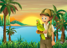 Ein Junge mit einem Papageien am Riverbank Lizenzfreies Stockfoto