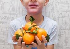 Ein Junge mit einem roten Hautausschlag auf seinen Backen und Lippen hält Orangen in seinen Händen Healh-Sorgfalt und Medizinkonz stockbilder