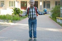 Ein Junge mit einem Rucksack, Büchern und einer Kugel geht zur Schule nach einem langen Sommer Lizenzfreies Stockfoto
