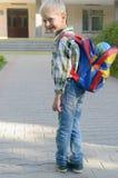 Ein Junge mit einem Rucksack, Büchern und einer Kugel geht zur Schule nach einem langen Sommer Stockbilder