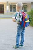 Ein Junge mit einem Rucksack, Büchern und einer Kugel geht zur Schule nach einem langen Sommer Lizenzfreie Stockfotos