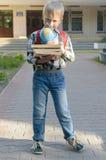 Ein Junge mit einem Rucksack, Büchern und einer Kugel geht zur Schule nach einem langen Sommer Lizenzfreies Stockbild