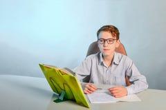 Ein Junge mit Gläsern sitzt hinter Lehrbüchern und denkt an das Lösen von Problemen lizenzfreie stockbilder