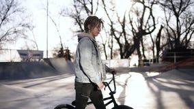 Ein Junge mit kurzen Dreadlocks im Rochenpark wak, das durch sein bmx Fahrrad lking ist sonniges Wetter Seitenansichtgesamtl?nge stock video