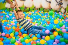 Ein Junge mit Mutter im spielenden Raum mit vielen kleinen farbigen Bällen Stockbilder
