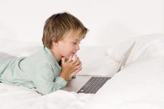 Ein Junge mit Notizbuch liegt auf einem Bett Stockfotografie