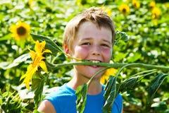 Ein Junge mit Sonnenblume Stockfotografie