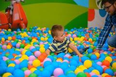 Ein Junge mit Vater im spielenden Raum mit vielen kleinen farbigen Bällen Stockfoto