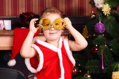 Ein Junge mit verzierten Gläsern im Silvesterabend Stockbild
