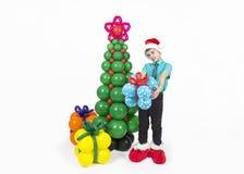 Ein Junge mit Weihnachtsbaum und Ballongeschenken Stockbild