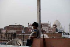 Ein Junge passt einen Drachen auf, der mit Taj Mahal im Hintergrund geflogen wird stockfotografie