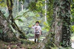 Ein Junge playng in einem tropischen Wald in der Talreserve Borneos Danum Lizenzfreie Stockfotografie