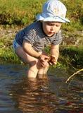 Ein Junge sammelt Schilfe auf dem Ufer von einem See Lizenzfreies Stockfoto