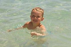 Ein Junge, schwimmend in einem Meer Stockbild